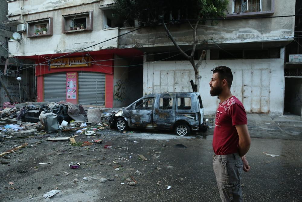 Um palestino examina uma rua na Cidade de Gaza após uma noite de pesado bombardeio aéreo por Israel. Os intensos bombardeios aéreos e terrestres de Israel fizeram com que pessoas em Gaza sofressem ferimentos físicos e psicológicos. Palestina, maio de 2021. © FADY HANONA