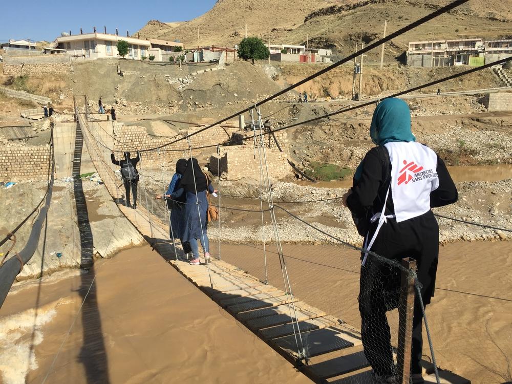 Equipe médica de MSF cruzando a ponte de corda Kyan Abad para implantar uma clínica móvel na vila de Paran Parvis, na margem do rio Kashkan (Sacha Petiot-Smigieski / MSF).