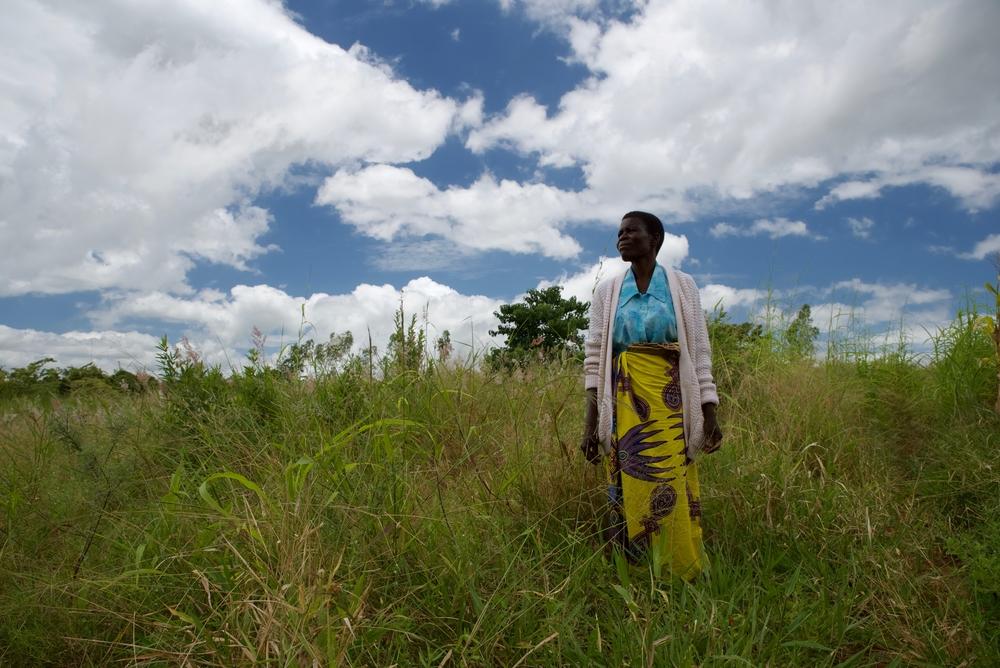 A paciente de câncer cervical Elida Howa olhando para os campos onde ela costumava cultivar antes de ficar doente, no distrito de Blantyre. Malaui, março de 2020. © FRANCESCO SEGONI/MSF