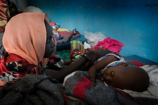 Bétel cuida de seu irmão mais novo de oito meses, Hassane Hano, que está recebendo tratamento para desnutrição.