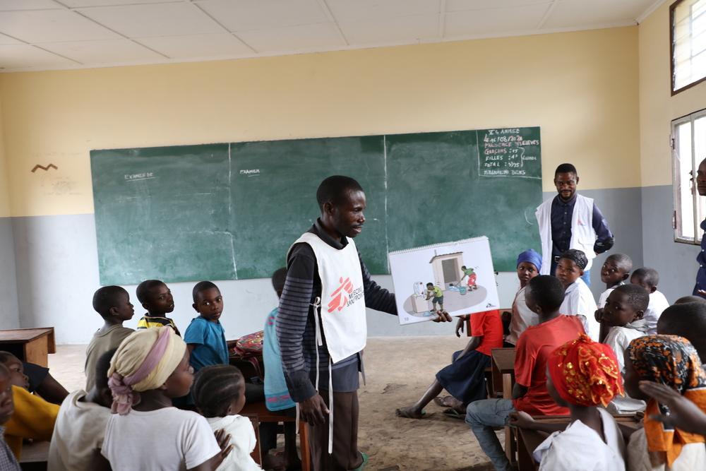 Equipe de promoção da saúde de MSF informando à população de Popokabaka sobre o surto de febre tifóide, seus sintomas e como evitá-lo. Foto por: Franck Ngonga