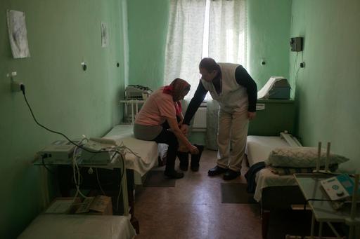 Idosa durante consulta em clínica móvel de MSF no vilarejo de Uspenka, em Donetsk (Foto: Amnon Gutman)