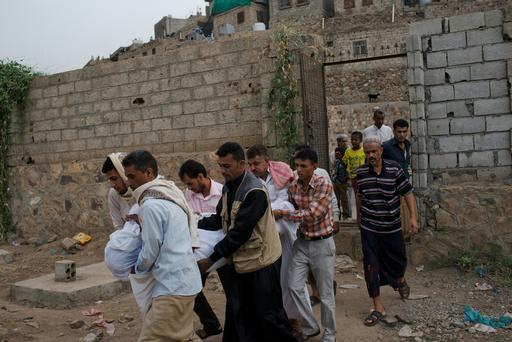 Família carrega o corpo de um ente querido após bombardeios atingirem residência em Taiz