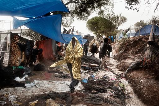 Refugiados e migrantes andam em meio ao lixo e à lama enquanto esperam para serem registrados no centro de Moria (Foto: Alessandro Penso)