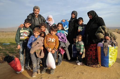 Uma família de Idlib, na Síria, cruzando a fronteira da Macedônia com a Sérvia (Foto: Florian Lems/MSF)