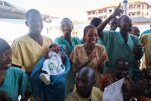 Profissionais de MSF cercam a bebê Nubia após a notícia de sua alta do centro de tratamento de Ebola de MSF em Conacri (Foto: Sam Phelps)