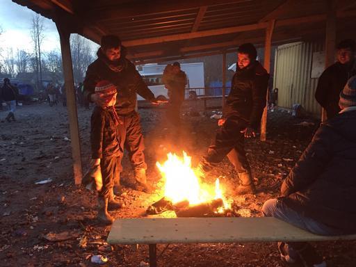 Refugiados acendem fogueira para se manterem aquecidos em acampamento. (Foto: Mohammad Ghannam/MSF)