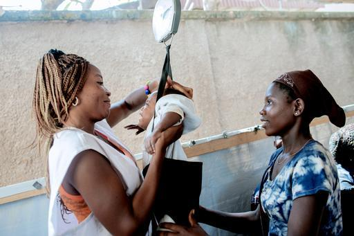 Profissional de MSF pesa o bebê da jovem Mireil Bozanga no campo de deslocados de Benzvi, em Bangui, capital da RCA (Foto: Luca Sola)