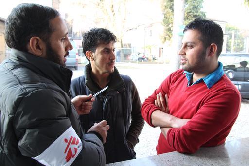 Profissional de MSF fala com migrantes sobre sua jornada pelos Balcãs (Foto: Sara Creta/MSF)