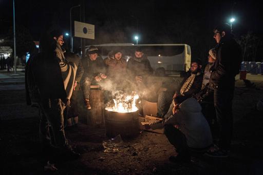 Sírios tentam se aquecer ao redor de uma fogueira em Polykastro, perto de Idomeni, na Grécia (Foto:  Konstantinos Tsakalidis/SOOC)