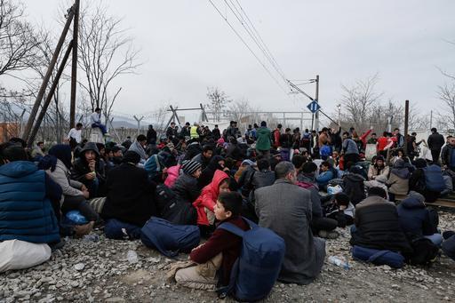 Afegãos sentados na linha do trem enquanto protestam próximo à fronteira da Grécia com a Macedônia (Foto: Konstantinos Tsakalidis/SOOC)