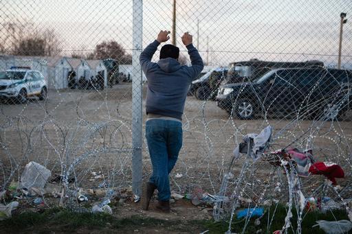 Homem olha pela cerca que o impede de atravessar a fronteira com a Macedônia (Foto: Alex Yallop/MSF)