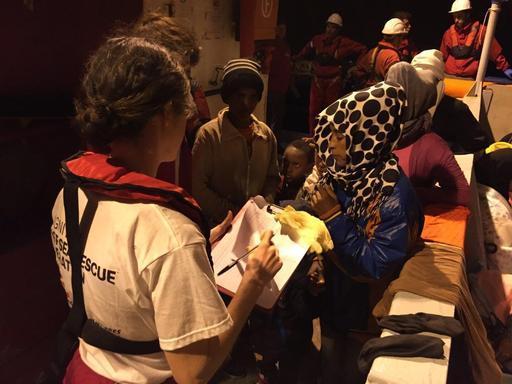 Tripulação de MSF recebe algumas pessoas transferidas para o Dignity I após serem resgatadas no meio do Mediterrâneo (Foto: Juan Matias Gil/MSF)