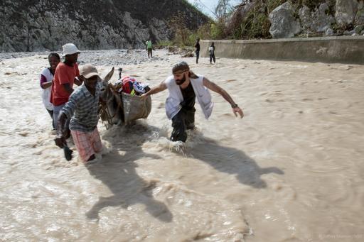 Haitianos e profissionais de MSF conduzem um burro para levar suprimentos até clínica móvel em Port à Piment (Foto: Joffrey Monnier / MSF)