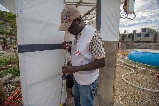 O agente de água e saneamento de MSF Pierre Emmanuel Hyppolite mede a turbidez da água para verificar seu nível de pureza