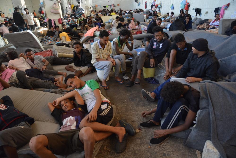 Migrantes e refugiados em centros de detenção na Líbia.