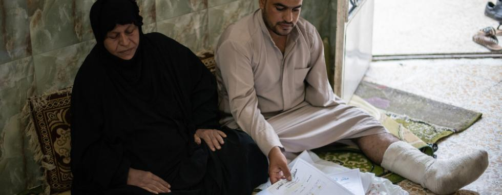 Hameeda e seu filho examinam seus arquivos médicos. Foto por: Chloe Sharrock / MSF