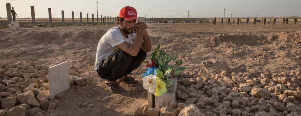 Ismael olha o túmulo de seu amigo que foi morto por um atirador do Estado islâmico na batalha por Raqqa