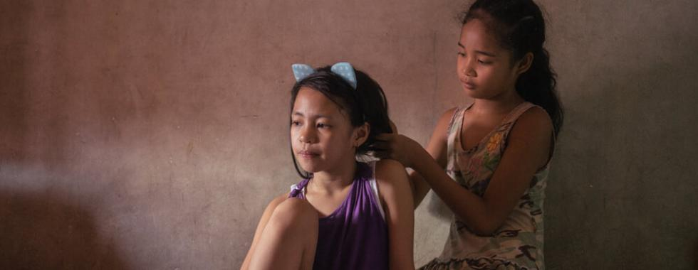 Menina penteia o cabelo da outra antes de posar para um retrato em sua casa em Manila