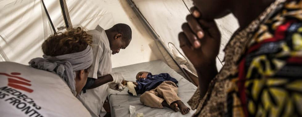 Enfermeiras de MSF examinam uma criança no centro de tratamento de cólera na República Democrática do Congo