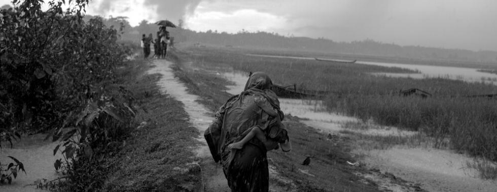Refugiados Rohingya buscam abrigo das chuvas de monção em um campo de arroz