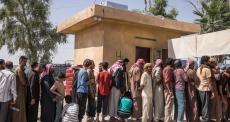 Fila para a documentação de saída do acampamento de deslocados de Ayn Issa.