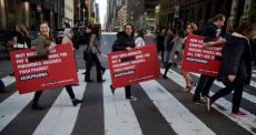 Pessoas atravessando faixa de pedestre carregando cartazes