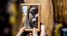 Mulher olha seu reflexo em espelho em clínica pré-natal de MSF no Níger